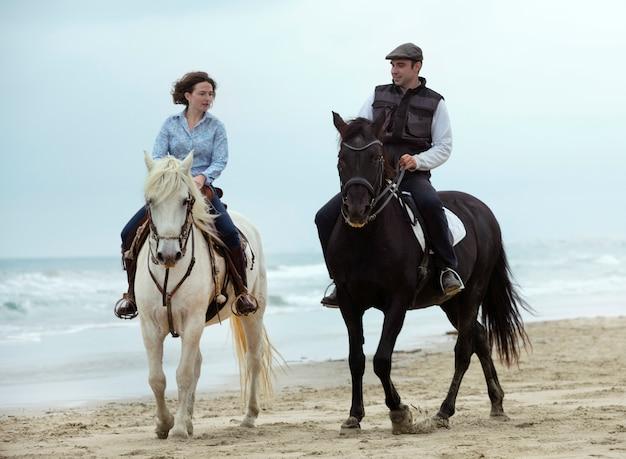 Reiter und pferde am strand Premium Fotos
