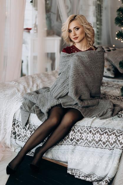 Reizend blondine umhüllt sich im grauen plaid, das auf einem bett vor einem weihnachtsbaum sitzt Kostenlose Fotos