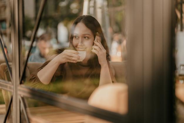 Reizend brunettefrau mit dem langen gelockten haar, das am fenster im café mit handy und kaffee in den händen sitzt Premium Fotos