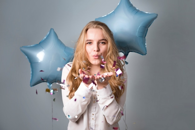 Reizend frau mit den ballonen, die am confetti durchbrennen Kostenlose Fotos