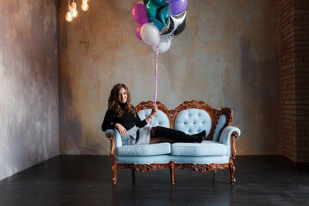 Reizend junge brunettefrau, die ein großes bündel heliumballone hält Kostenlose Fotos