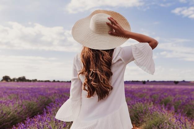 Reizend junge frau mit einem hut und einem weißen kleid auf einem purpurroten lavendelgebiet bei sonnenuntergang Premium Fotos