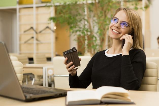 Reizend junge geschäftsfrau, die im büro arbeitet Premium Fotos