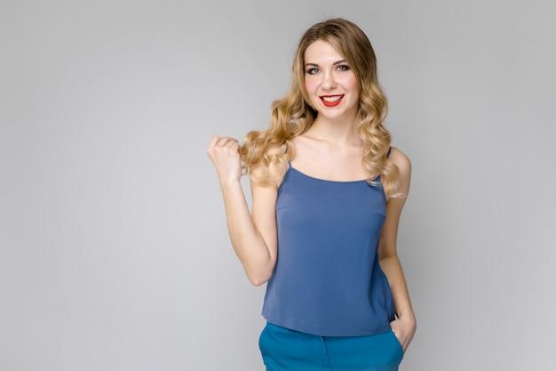 Reizend junges blondes mädchen in der blauen kleidung lächelnd auf grauer wand Premium Fotos