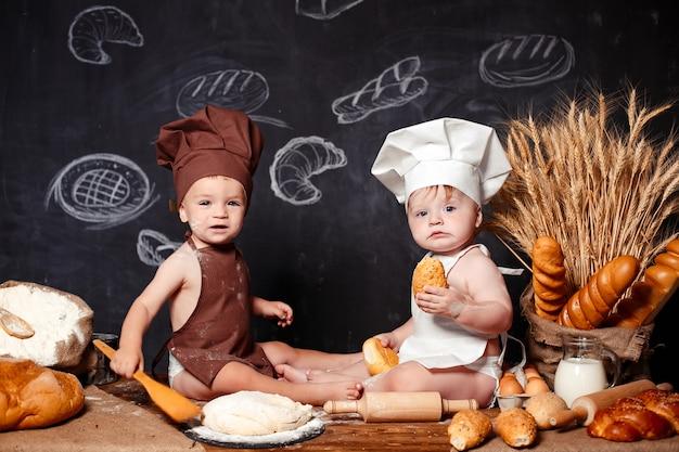 Reizend kleine kleinkinder in den schutzblechen auf tabelle mit brot Premium Fotos