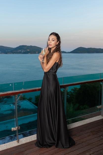 Reizend schönes mädchen, das in der hand in einem schokoladenabendkleid mit einem glas champagner aufwirft Premium Fotos