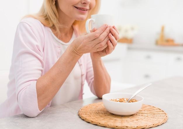 Reizende ältere frau der nahaufnahme, die frühstückt Kostenlose Fotos
