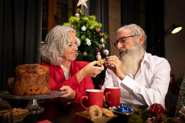 Reizende ältere paare, die weihnachtsplätzchen essen Kostenlose Fotos