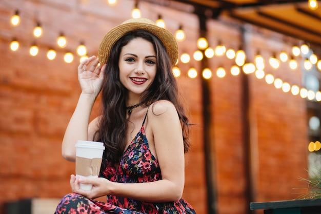 Reizende brunettefrau mit dunklen augen und den roten lippen ihre freizeit an der cafeteria genießend, heißen tee oder kaffee trinkend Premium Fotos