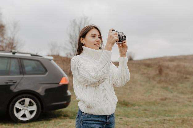 Reizende frau, die draußen foto macht Kostenlose Fotos
