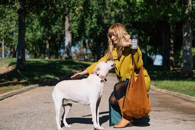 Reizende Frau mit dem streichelnden Hund der Thermosflasche Kostenlose Fotos