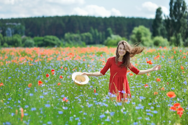 Reizende junge romantische frau im strohhut auf mohnblumenblumenfeld Premium Fotos