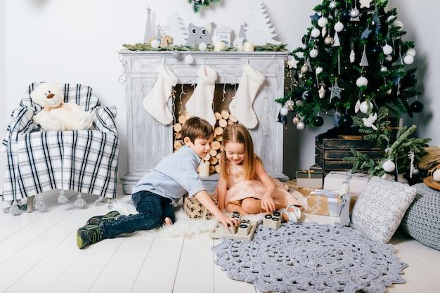 Reizende kinder, die im raum mit weihnachtsbaum und kamin spielen. winterurlaub-konzept. Premium Fotos