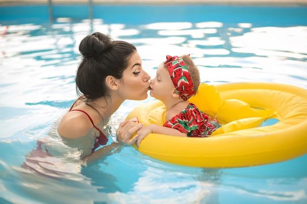 Reizende mutter, die ihr baby beim schwimmen im swimmingpool küsst Premium Fotos