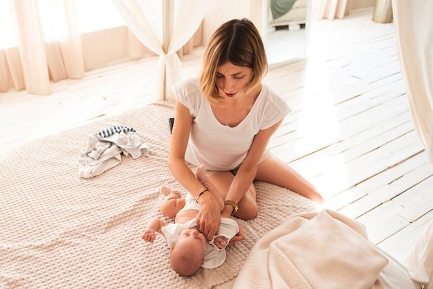 Reizende mutter, die neugeborenes baby kleidet Kostenlose Fotos