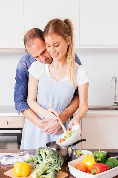 Reizender junger mann, der seine frau liebt, die das lebensmittel in der küche zubereitet Kostenlose Fotos