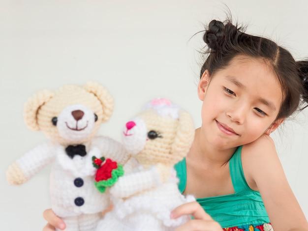 Reizendes asiatisches kind spielt hochzeitsbärnpuppen Kostenlose Fotos