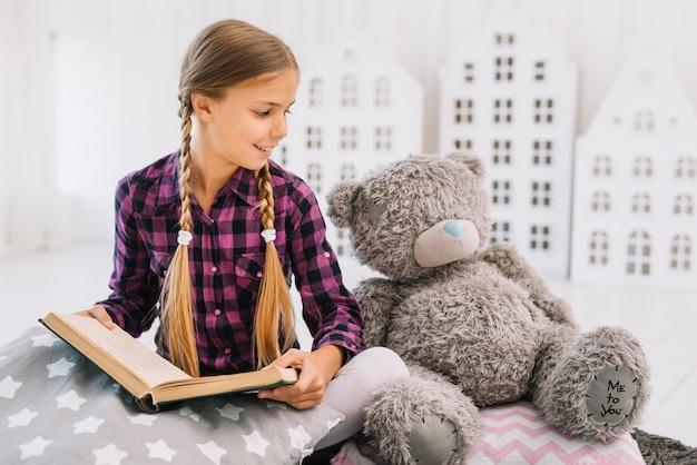 Reizendes kleines mädchen, das ein buch mit ihrem teddybären liest Kostenlose Fotos