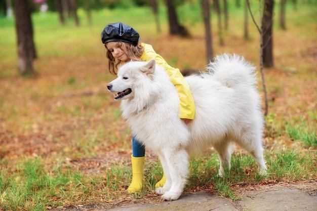 Reizendes mädchen auf einem weg mit einem schönen hund in einem park im freien Premium Fotos