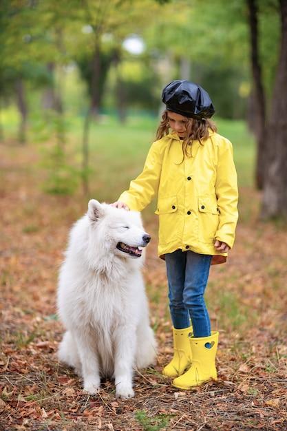Reizendes mädchen in den gelben gummistiefeln und im regenmantel auf wege, spielt mit einem schönen weißen samoyedhund im herbstpark Premium Fotos