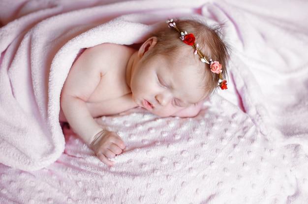 Reizendes neugeborenes mädchen, das auf rosa decke schläft Premium Fotos