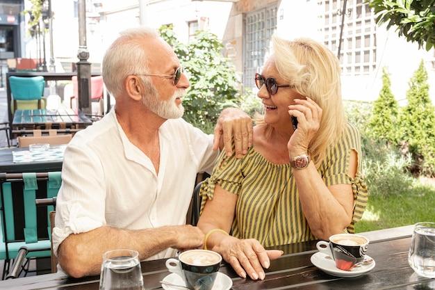 Reizendes paar, das einander durch eine tabelle betrachtet Kostenlose Fotos