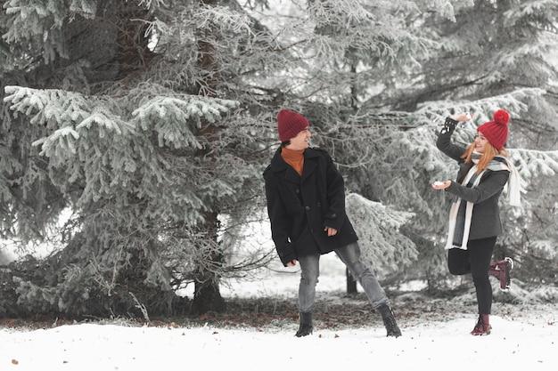 Reizendes paar, das mit schneekatze spielt Kostenlose Fotos