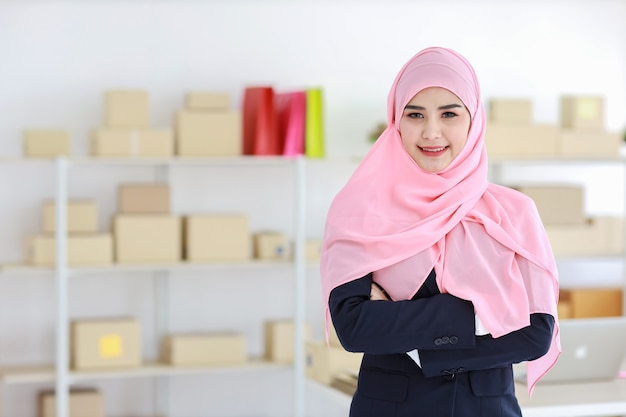 Religiöse asiatische muslimische frau im blauen anzug und im rosa schaft auf kopf stehend und kamera mit vertrauen betrachtend Premium Fotos