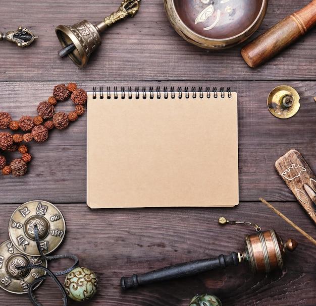 Religiöse musikinstrumente für meditation und alternativmedizin, leeres notizbuch mit braunen blättern Premium Fotos