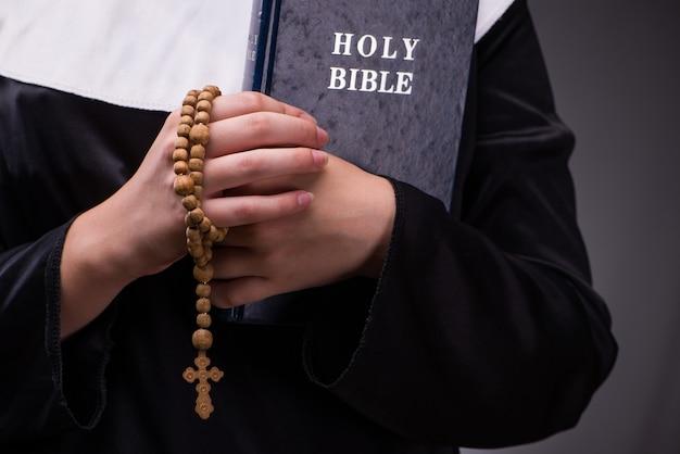 Religiöse nonne im religionskonzept gegen dunklen hintergrund Premium Fotos