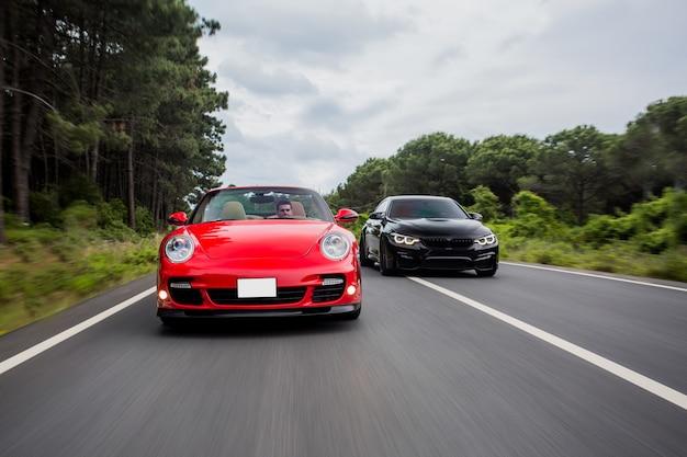 Rennen auf der autobahn zwischen schwarzen und roten coupé-autos. Kostenlose Fotos