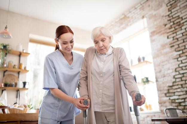 Rentner, der mit krücken geht, die nahe pflegekraft stehen Premium Fotos