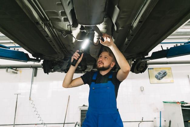 Reparateure, die unterseite des autos mit lampe überprüfen Kostenlose Fotos