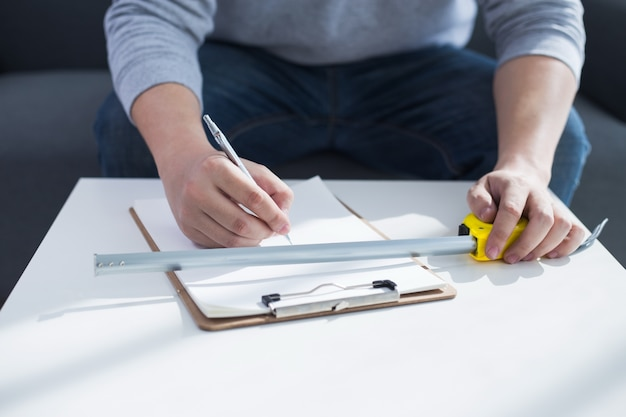 Reparatur, gebäude und home-konzept - nahaufnahme von männlichen händen schriftlich in zwischenablage Kostenlose Fotos