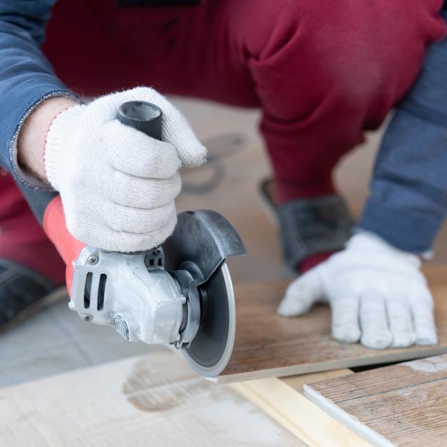 Reparatur und dekoration. ein mann schneidet keramikfliesen mit einer mühle. Premium Fotos