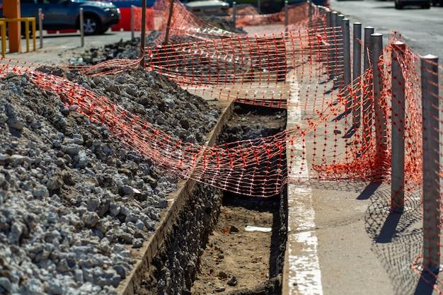 Reparaturarbeiten an der stadtstraße. ein frisch gegrabener graben ist zur sicherheit der bürger mit einem netz eingezäunt. Premium Fotos
