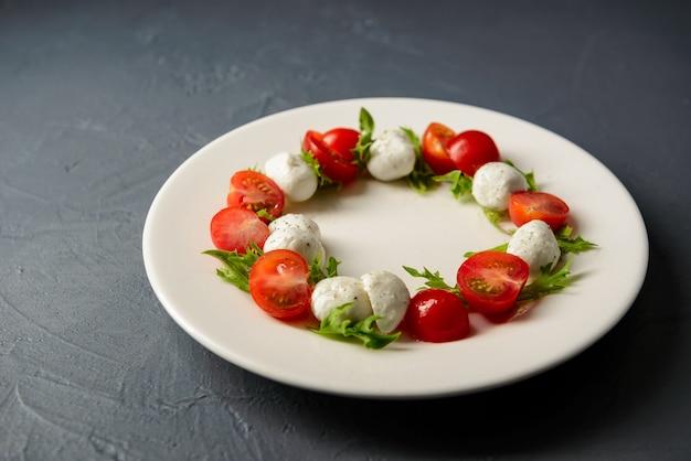 Restaurant serviert köstlichen und gesunden caprese-salat auf weißem teller Kostenlose Fotos