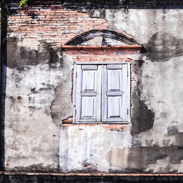 Retro- altes gealtertes fenster der weinlese und braune farbe maserten lehmziegelsteinblockwand Premium Fotos