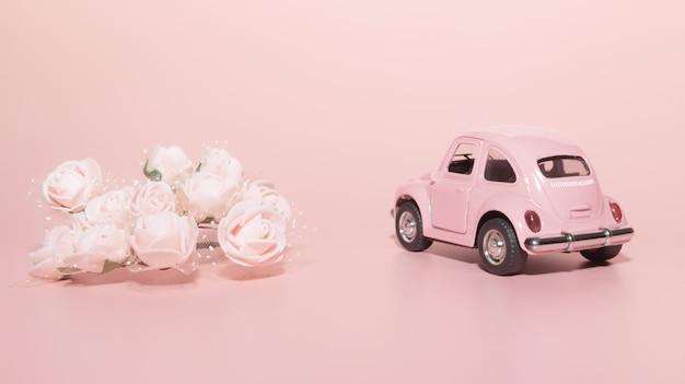 Retro- auto des rosa spielzeugs auf rosa hintergrund, nahe bei weißen rosen Premium Fotos