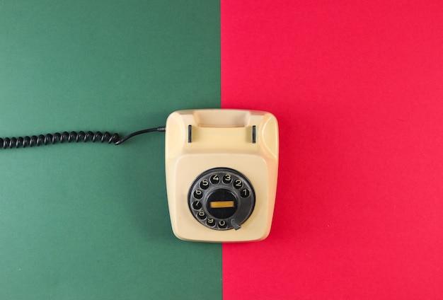 Retro-drehtelefon auf einer rot-grünen papieroberfläche. Premium Fotos