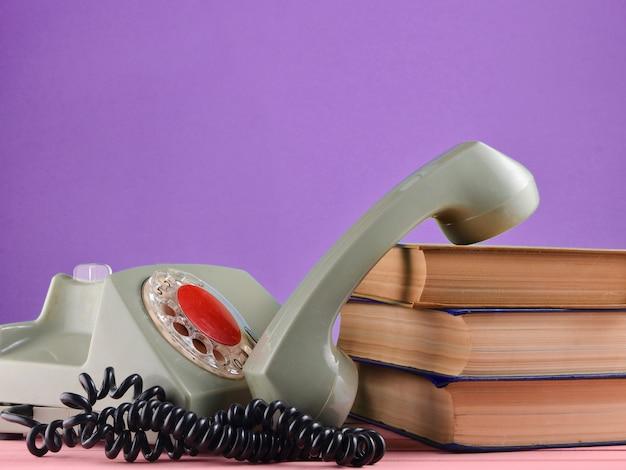 Retro-drehtelefon, stapel bücher auf einem schreibtisch lokalisiert gegen eine lila pastellwand Premium Fotos