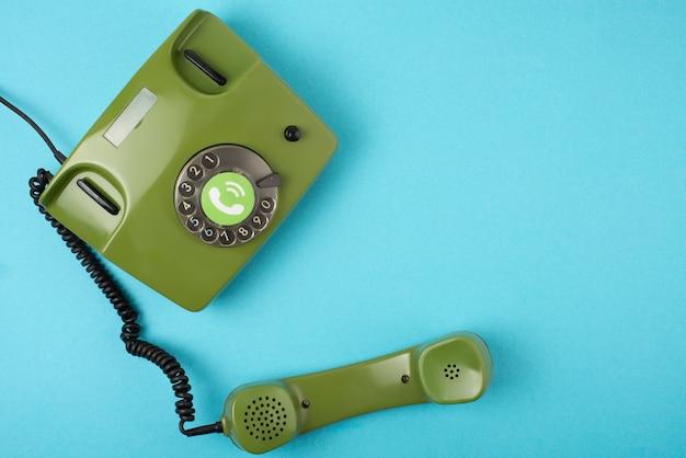 Retro- grünes telefonfoto auf einem blauen hintergrund Premium Fotos