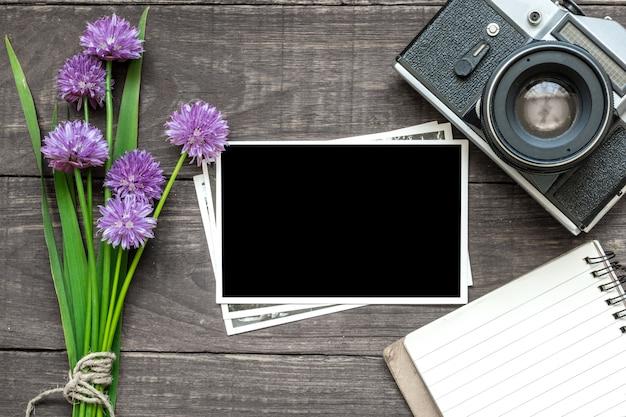 Retro- kamera der weinlese mit leerem fotorahmen, purpurroten wildflowers und gezeichnetem notizbuch auf rustikalem holztisch Premium Fotos