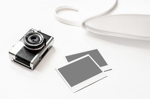 Retro kamera flatlay-weinlese auf hölzernem weißem hintergrund mit leerem foto des sofortigen papiers Premium Fotos
