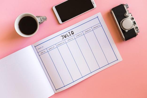 Retro kamera in der nähe von smartphone, cup und kalender Kostenlose Fotos
