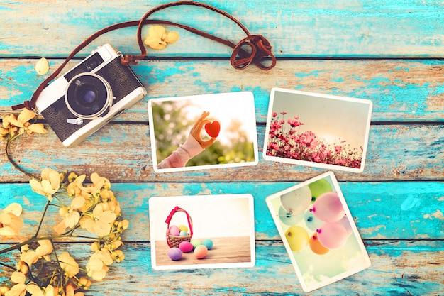 Retro- kamera- und papierfotoalbum auf hölzerner tabelle mit blumen Premium Fotos