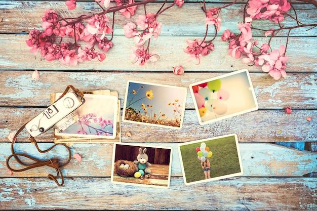 Retro- kamera- und papierfotoalbum auf hölzerner tabelle mit blumengrenzdesign Premium Fotos
