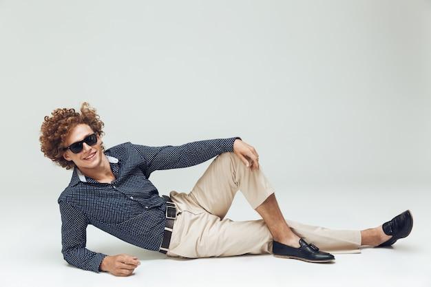 Retro mann gekleidet im hemd liegt auf boden und posiert Kostenlose Fotos
