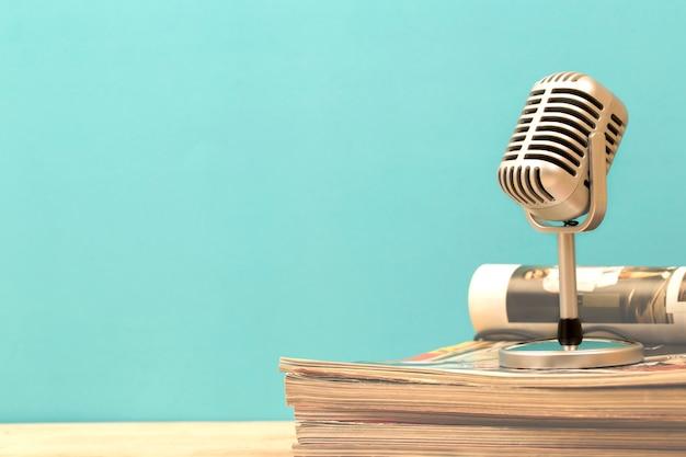 Retro- mikrofon mit alter zeitschrift auf holztisch Premium Fotos