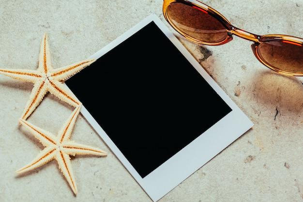 Retro sonnenbrille und leere polaroidfotorahmen, muscheln Premium Fotos